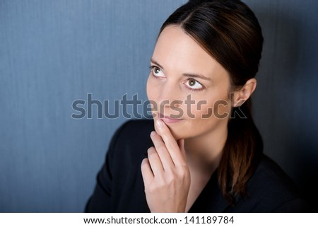 Closeup of thoughtful businesswoman looking up with hand on chin against blue wall - stock photo