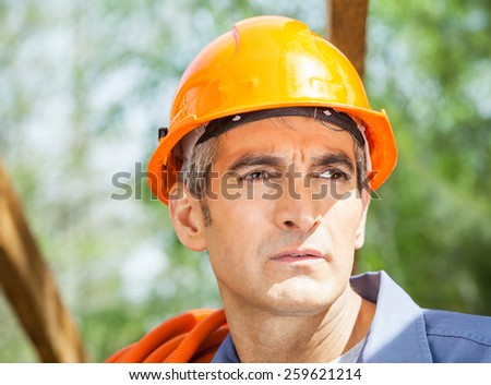 Closeup of thoughtful male construction worker looking away at site - stock photo