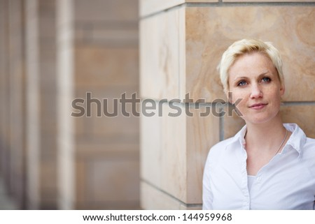 Closeup of thoughtful woman looking away while leaning on pillar - stock photo