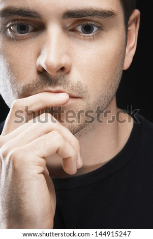 Closeup of thoughtful young man with finger on lips over black background