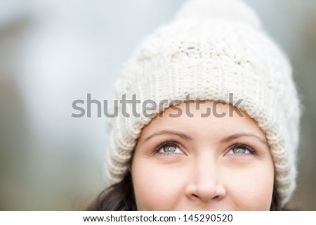 Closeup of thoughtful young woman wearing knit hat while looking up - stock photo