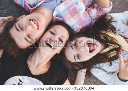 Closeup of three best friends lying down and laughing. Teenage people wearing casual clothes smiling. Top view - stock photo