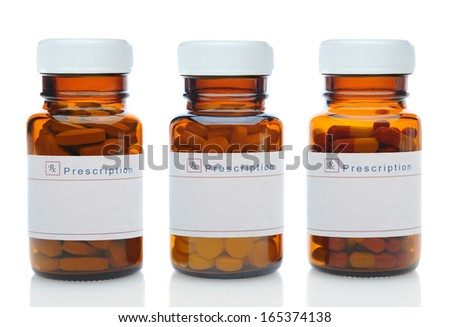 Closeup of three brown medicine bottles filled with different pills and medications with their caps on over a white background with reflection.  - stock photo