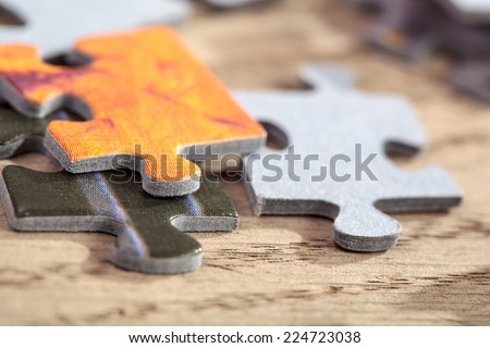 Closeup of  three connected jigsaw puzzle pieces on a table. Shallow depth of field - stock photo
