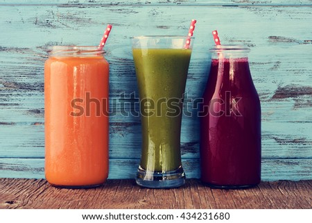closeup of three different fresh smoothies served in a glass, a glass jar and a glass bottle with red drinking straws patterned with white dots, on a rustic wooden surface - stock photo