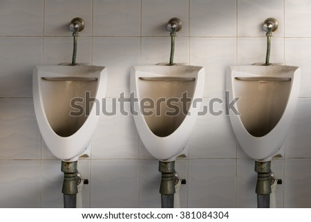 closeup of three dirty white urinals in men's bathroom, design of white ceramic urinals for men in toilet room, toilet, toilet shot, dirty toilet, urinate, urinate in a toilet, gent urinate toilet - stock photo