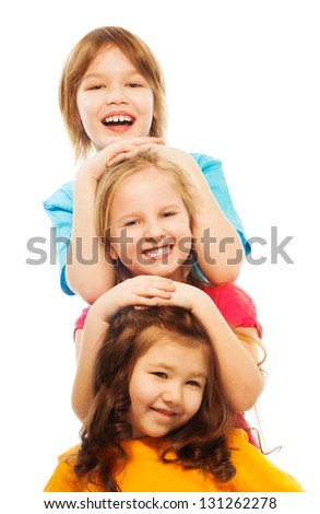 Closeup of three diversity looking kids in a row one on top of another in a vertical line, smiling, happy, smiling, isolated on white