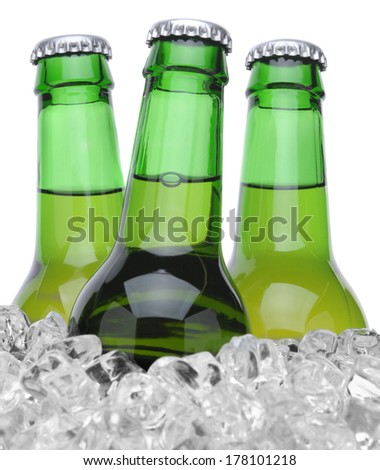 Closeup of three green beer bottles in ice isolated on white horizontal format - stock photo