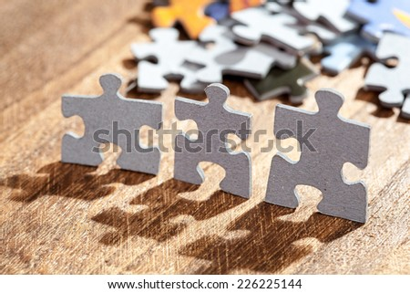 Closeup of three jigsaw puzzle pieces on a table lit by back light. Shallow depth of field