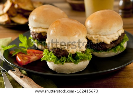 Closeup of three mini burgers with lettuce, cheese and spicy remoulade. - stock photo