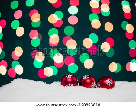 closeup of three red colored christmas globes decorated with glittery snowflakes surrounded with snow with colorful christmas lights on background - stock photo
