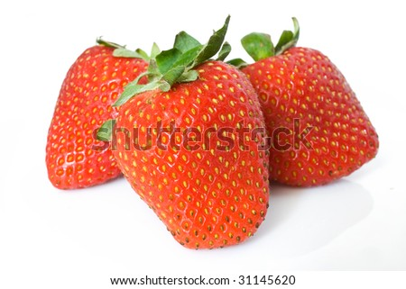 closeup of three ripe strawberries isolated on white background