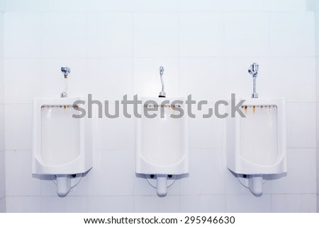 Closeup of three white urinals in men's bathroom, design of white ceramic urinals for men in toilet room - stock photo