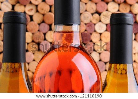 Closeup of three wine bottles two chardonnay and one red in front of a mass of out of focus corks. - stock photo