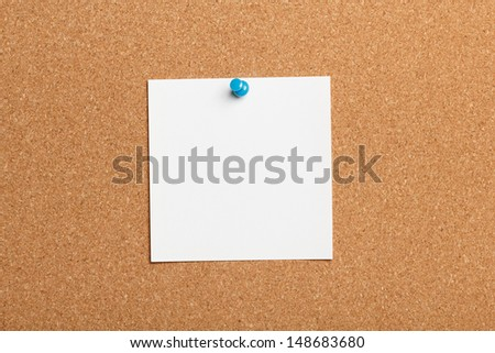 Closeup of thumbtack and note on cork billboard - stock photo