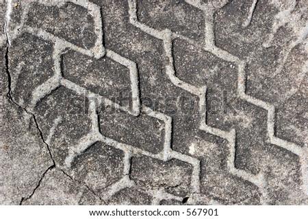 Closeup of tire track in concrete. - stock photo