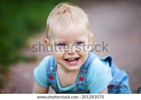 Closeup of toddler boy crawling outdoors - stock photo