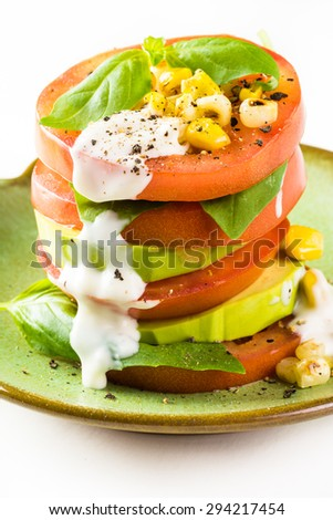 Closeup of tomato stack salad with corn and avocado on a white background.
