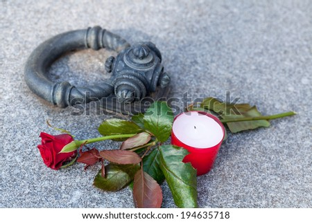 Closeup of tombstone with single rose and candle - stock photo