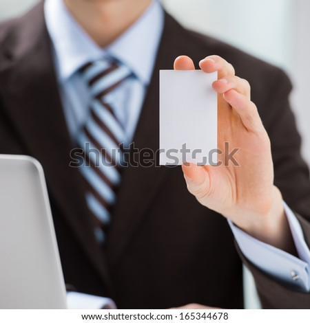 Closeup of torso of confident business man wearing elegant suit sharing his blank business card at his workplace. Vertical - stock photo
