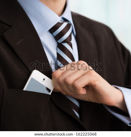Closeup of torso of confident business man wearing elegant suit taking mobile phone from pocket - stock photo
