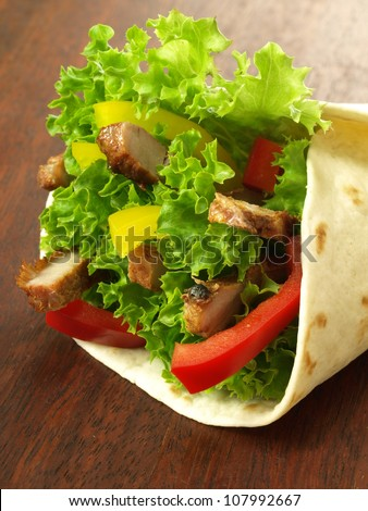 Closeup of tortilla wrap with meat and vegetables