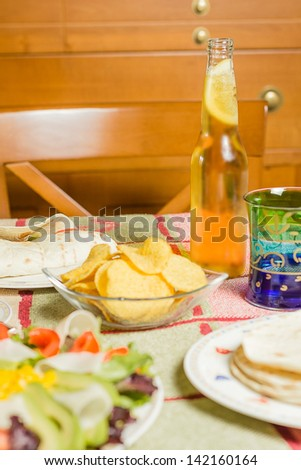 Closeup of traditional mexican food in a table, with  a bowl of nachos, a plate of chicken fajita, tortillas, fresh salad and a fresh beer - stock photo