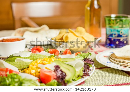 Closeup of traditional mexican food in a table, with a plate of fresh salad, tortillas, chicken fajitas, nachos and a bowl of spicy sauce