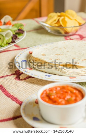 Closeup of traditional mexican food in a table, with a plate of tortillas, fresh salad, nachos and a bowl of spicy sauce - stock photo