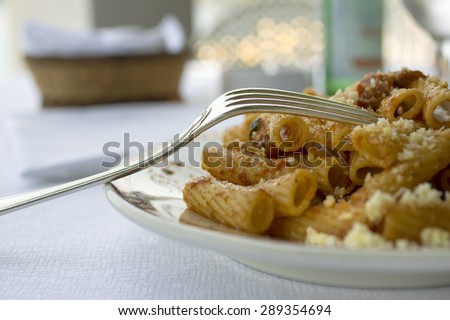 Closeup of traditional tortiglioni sitting on a plate with a fork sticking out on left. Outdoor shot with particular focus. - stock photo
