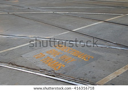 Closeup of tramway with yellow signage â??Pedestrians give way to tramsâ? in between rail tracks on concrete road in Melbourne, Australia - stock photo