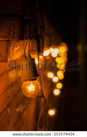 Closeup of tungsten lamp decorated on brick wall with bokeh light background.. - stock photo