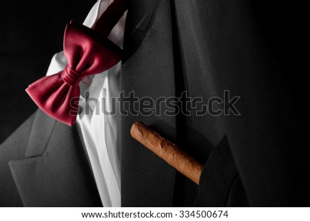 Closeup of tuxedo with shirt and bow-tie with cigar in chest pocket.