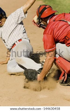 Closeup of two baseball players at home base - stock photo