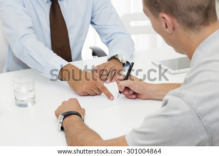 Closeup of two business partners  signing a document. - stock photo