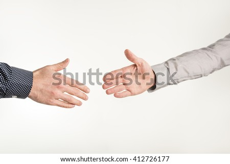Closeup of two businessmen about to shake hands in a handshake over white background.