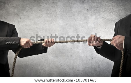 Closeup of two businessmen playing tug of war