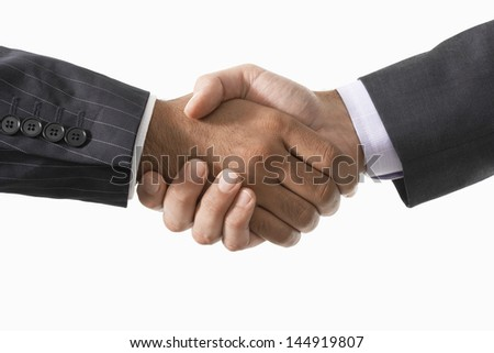 Closeup of two businessmen shaking hands against white background
