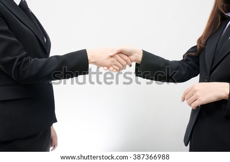 Closeup of two businesswomen, lawyers or politicians shaking hands to celebrate a successful agreement with one of them holding the other hand in his pocket. Isolated over white background.