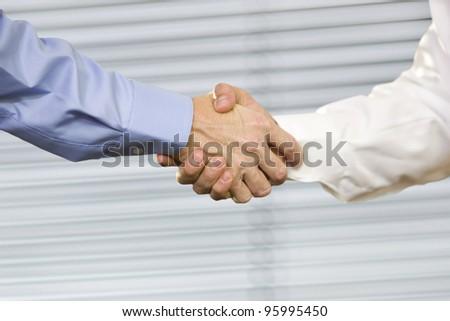 Closeup of two Caucasian men shaking hands. - stock photo