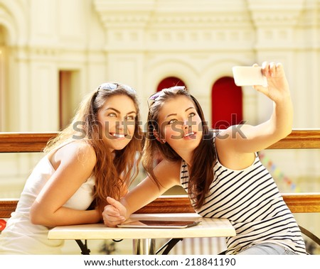 Closeup of two cheerful friends having fun and taking photos of themselves on smart phone. - stock photo