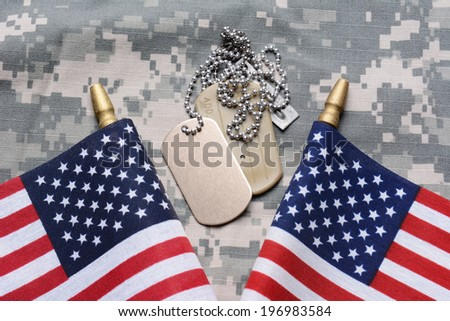 Closeup of two crossed American Flags on camouflage material with dog tags in the middle. The ID tags are blank. Horizontal format filling the frame. - stock photo