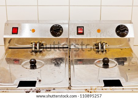 Closeup of two deep fryers in front of white tiles in a kitchen