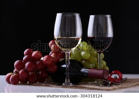 Closeup of two glasses with red and white wine standing on burlap napkin near green and red grapes bunches and lying new uncorked bottle and corkscrew on black background, horizontal picture