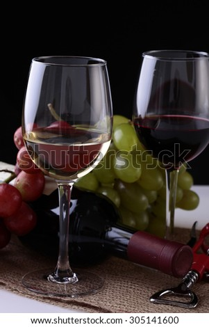 Closeup of two glasses with red and white wine standing on burlap napkin near green and red grapes bunches and lying new uncorked bottle and corkscrew on black background, vertical picture