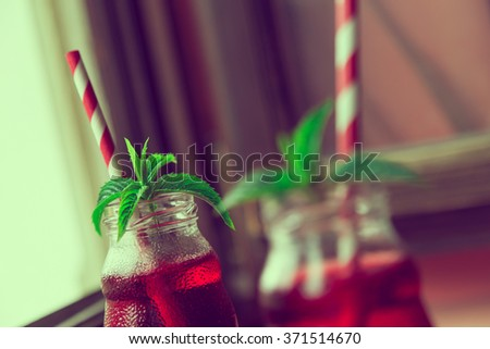 Closeup of two jars with organic raspberry juice, with striped red and white drinking straws and fresh mint leaves in it, placed to a table next to a restaurant window - stock photo