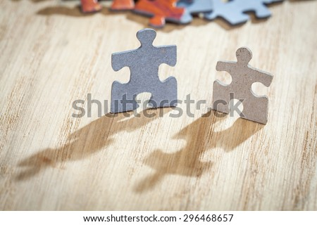 Closeup of two jigsaw puzzle pieces on table. Shallow depth of field