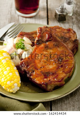 Closeup of two juicy barbecued pork cops with corn and potato salad.