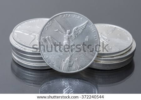 Closeup of two small stacks and front of Mexican silver bullion coins on reflective surface - stock photo