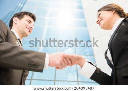 Closeup of two successful smiling business people shaking hands.